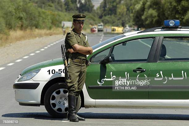 An Algerian policeman stands guard as security forces block the road to Lakhdaria 70 kilometres southeast of Algiers where a suicide bomber rammed an...