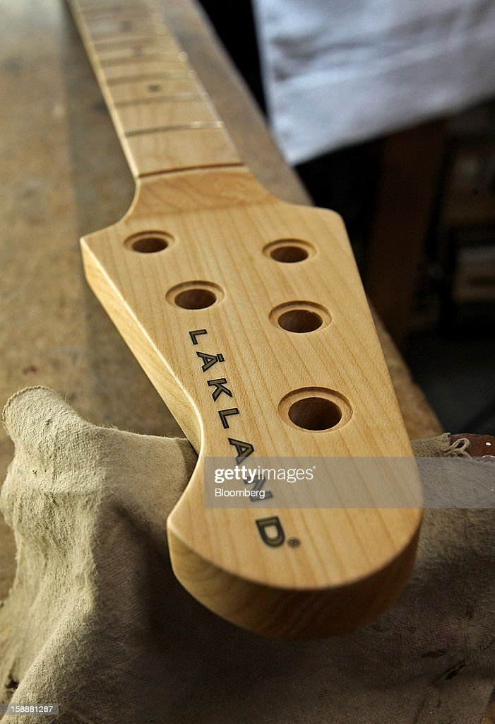 A Lakland bass guitar headstock rests on a bench at the company's production facility in Chicago, Illinois, U.S., on Thursday, Dec. 27, 2012. Manufacturing picked up in December, reflecting growth in orders, employment and exports that indicate the U.S. expansion will be sustained in 2013 following the budget deal. Photographer: Tim Boyle/Bloomberg via Getty Images