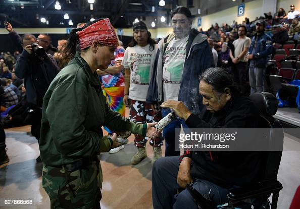 Lakota elder Leonard Crow Dog right receives a blessing of sage during an emotional forgiveness ceremony at the Four Prairie Knights Casino Resort on...