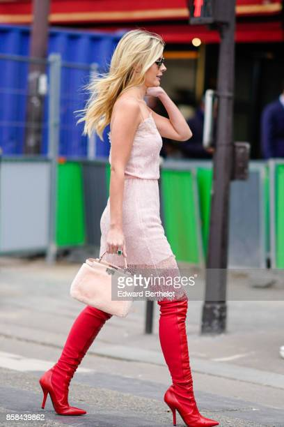 Lala Rudge wears a pink dress a pink bag red thigh high boots outside Giambattista Valli during Paris Fashion Week Womenswear Spring/Summer 2018 on...