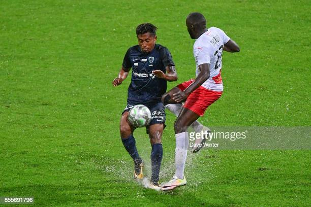 Lalaina Nomenjanahary of Paris FC and Sada Thioub of Nimes compete on a waterlogged pitch during the Ligue 2 match between Paris FC and Nimes on...