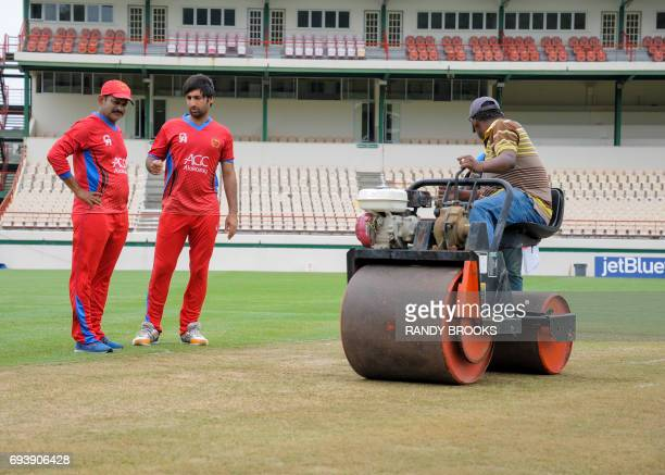 Lalchand Sitaram Rajput and Mohamad Asghar Stanikzai of Afghanistan chat about the pitch as ground staff use a roller during a training session at...