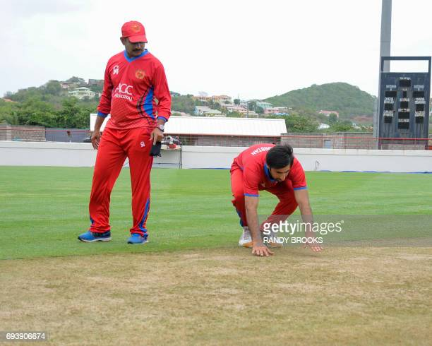 Lalchand Sitaram Rajput of Afghanistan watches as teammate Mohamad Asghar Stanikzai of Afghanistan inspects the pitch during a training session at...