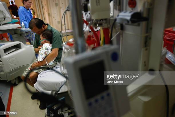Lam Nguyen comforts his oneyearold son Dylan in the emergency room of the nonprofit Children's Hospital on September 14 2009 in Aurora Colorado...