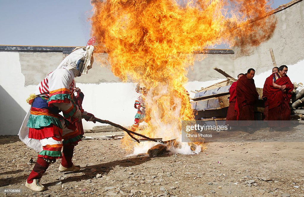 A lama burns a thing symbolizing evil spirits during the 'Tiaoqian' praying ceremony at the Youning Temple on February 8, 2009 in Huzhu County of Qinghai Province, China. The Youning Temple holds the annual 'Tiaoqian' ceremony in the first lunar month each year. During the ceremony, monks will wear colourful traditional clothes and masks, performing the 'Fawang Dance' and 'Horse-headed Warrior Dance' to scare away evil spirits. Pilgrims also pray for good luck during the ceremony.