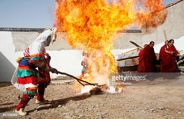 A lama burns a thing symbolizing evil spirits during the 'Tiaoqian' praying ceremony at the Youning Temple on February 8 2009 in Huzhu County of...