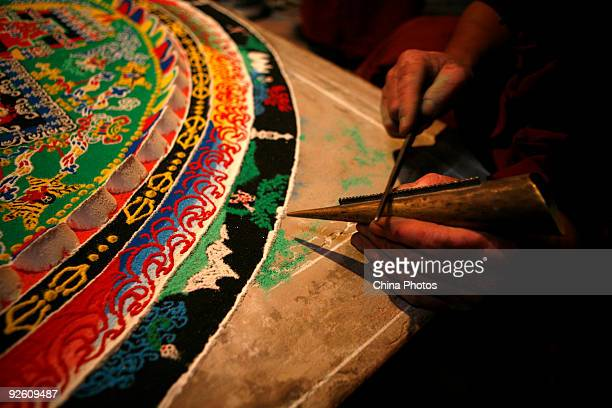 A lama makes a mandala sand painting which will be used for an enshrining ceremony at the Youning Temple on November 1 2009 in Huzhou County of...