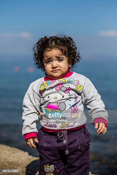 Lamar 2yearold girl from Syrian town El Haseke poses for a photograph after arriving with other migrants and refugees on the shores of the Greek...