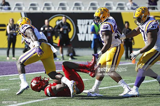Lamar Jackson of the Louisville Cardinals gets sacked in the first quarter of the Buffalo Wild Wings Citrus Bowl against the LSU Tigers at Camping...