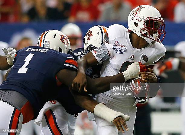Lamar Jackson of the Louisville Cardinals is tackled by Montravius Adams and Devonte Danzey of the Auburn Tigers at Georgia Dome on September 5 2015...