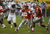 Lamar Jordan of the New Mexico Lobos pitches the ball to teammate Jhurell Pressley in front of Antonio Longino of the Arizona State Sun Devils during...
