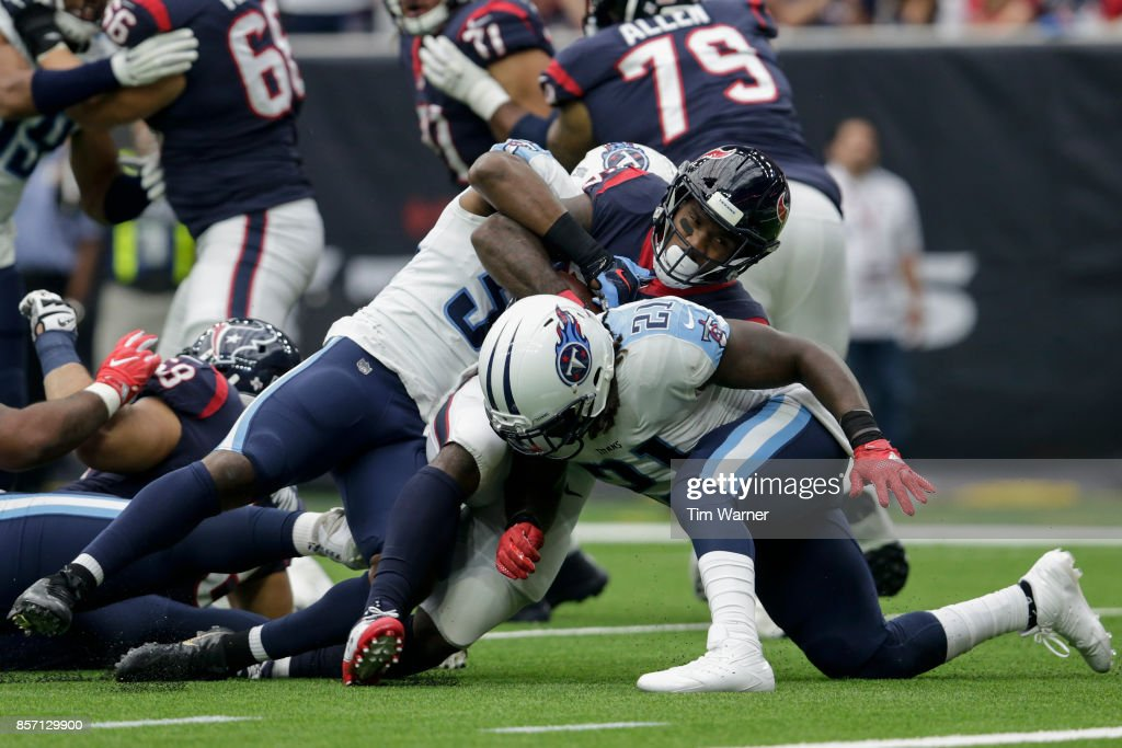 Lamar Miller #26 of the Houston Texans is tackled by Avery Williamson #54 of the Tennessee Titans and Da'Norris Searcy #21 in the first quarter at NRG Stadium on October 1, 2017 in Houston, Texas.