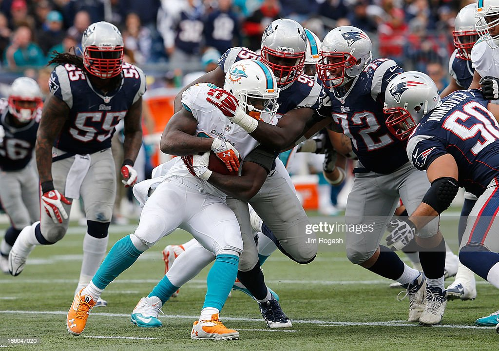Lamar Miller #26 of the Miami Dolphins is stopped by <a gi-track='captionPersonalityLinkClicked' href=/galleries/search?phrase=Chandler+Jones&family=editorial&specificpeople=7181843 ng-click='$event.stopPropagation()'>Chandler Jones</a> #95 of the New England Patriots in the first half at Gillette Stadium on October 27, 2013 in Foxboro, Massachusetts.