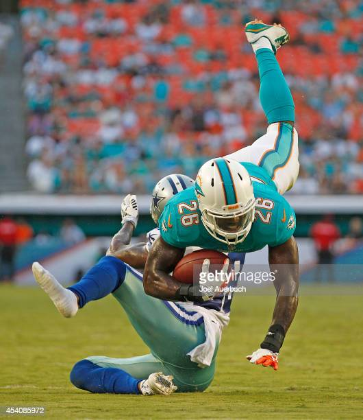 Lamar Miller of the Miami Dolphins is tackled by Brandon Carr of the Dallas Cowboys as he runs with the ball during a preseason game on August 23...
