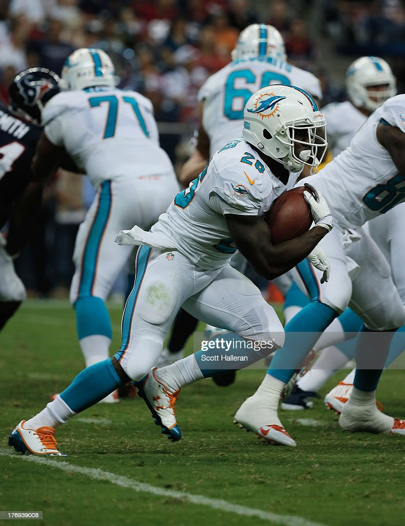 Lamar Miller #26 of the Miami Dolphins runs upfield against the Houston Texans during a preseaon game at Reliant Stadium on August 17, 2013 in Houston, Texas.