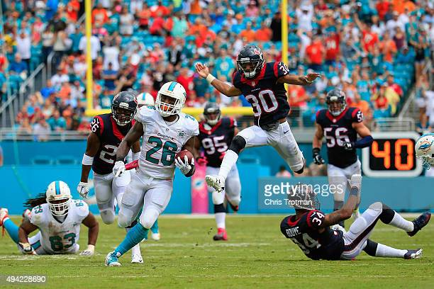 Lamar Miller of the Miami Dolphins runs with the ball for a touchdown in the second quarter against the Houston Texans at Sun Life Stadium on October...
