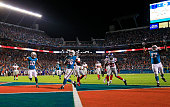 Lamar Miller of the Miami Dolphins scores a touchdown during the first quarter of the game against the New York Giants at Sun Life Stadium on...