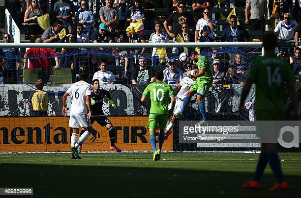 Lamar Neagle of Seattle Sounders FC heads the ball on goal as goalkeeper Jaime Penedo and AJ DeLaGarza of the Los Angeles Galaxy defend their goal in...