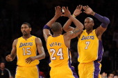 Lamar Odom and Kobe Bryant of the Los Angeles Lakers celebrate on the court as they stand next to teammate Ron Artest while taking on the New Orleans...