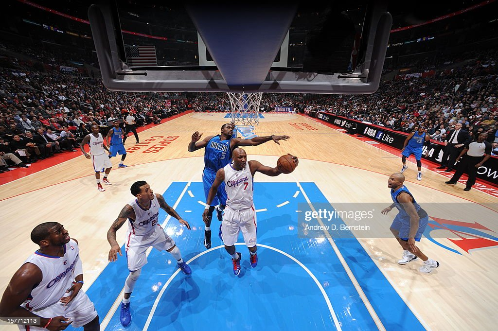 Lamar Odom #7 of the Los Angeles Clippers protects the ball from Bernard James #5 of the Dallas Mavericks during the game between the Los Angeles Clippers and the Dallas Mavericks at Staples Center on December 5, 2012 in Los Angeles, California.