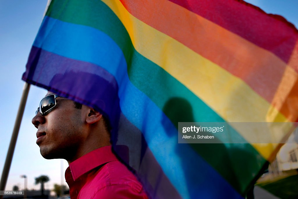 Lamar Smith right of West Covina is silhouetted by Minh Tran's left of Westminster gay pride flag as they join the Coalition of Vietnamese American...