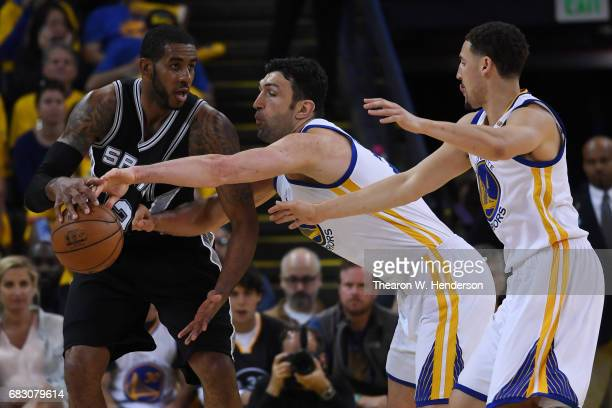 LaMarcus Aldridge of the San Antonio Spurs is defended by Zaza Pachulia of the Golden State Warriors during Game One of the NBA Western Conference...