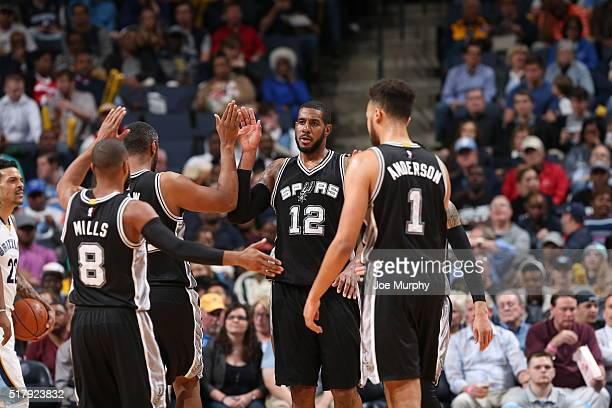 LaMarcus Aldridge of the San Antonio Spurs shakes hands with his teammates during the game against the Memphis Grizzlies on March 28 2016 at...