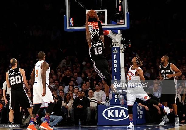LaMarcus Aldridge of the San Antonio Spurs slam dunks the ball in front of Derrick Williams of the New York Knicks during the first quarter at...