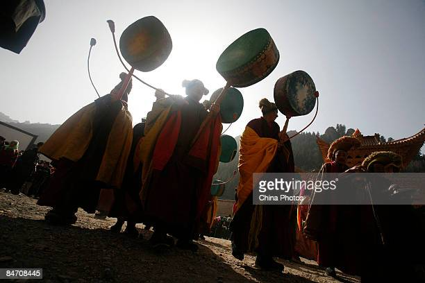 Lamas beat drums to scare away evil spirits during the 'Tiaoqian' praying ceremony at the Youning Temple on February 8 2009 in Huzhu County of...