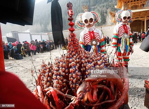Lamas guard the religious weapons as others present skull dance during the 'Tiaoqian' praying ceremony at the Youning Temple on February 8 2009 in...