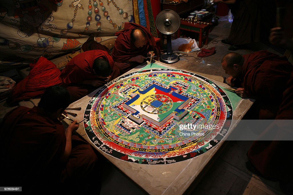 Lamas make a mandala sand painting, which will be used for an enshrining ceremony at the Youning Temple on November 1, 2009 in Huzhou County of Qinghai Province, China. Mandala sand painting, known as dul-tson-kyil-khor in Tibetan, which literally means 'mandala of colored powders', is a unique art of Tibetan Buddhism. The grains of sand are laid on a flat platform with special tools, forming iconography including geometric shapes and spiritual symbols, resulting in a work of art that usually takes a monk a couple of weeks or months to finish.