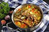 delicious Icelandic Lamb winter hot Soup with vegetables and spices or kjotsupa in a stainless steel casserole pan on wooden table with kitchen towel, traditional recipe, view from above, close-up