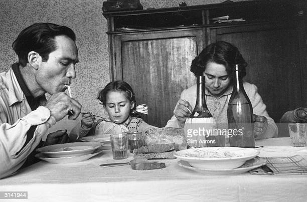 Lamberto Maggiorani star of Vittorio de Sica's film 'The Bicycle Thief' eating dinner with his wife Giuseppina and his daughter Paula at home in Rome