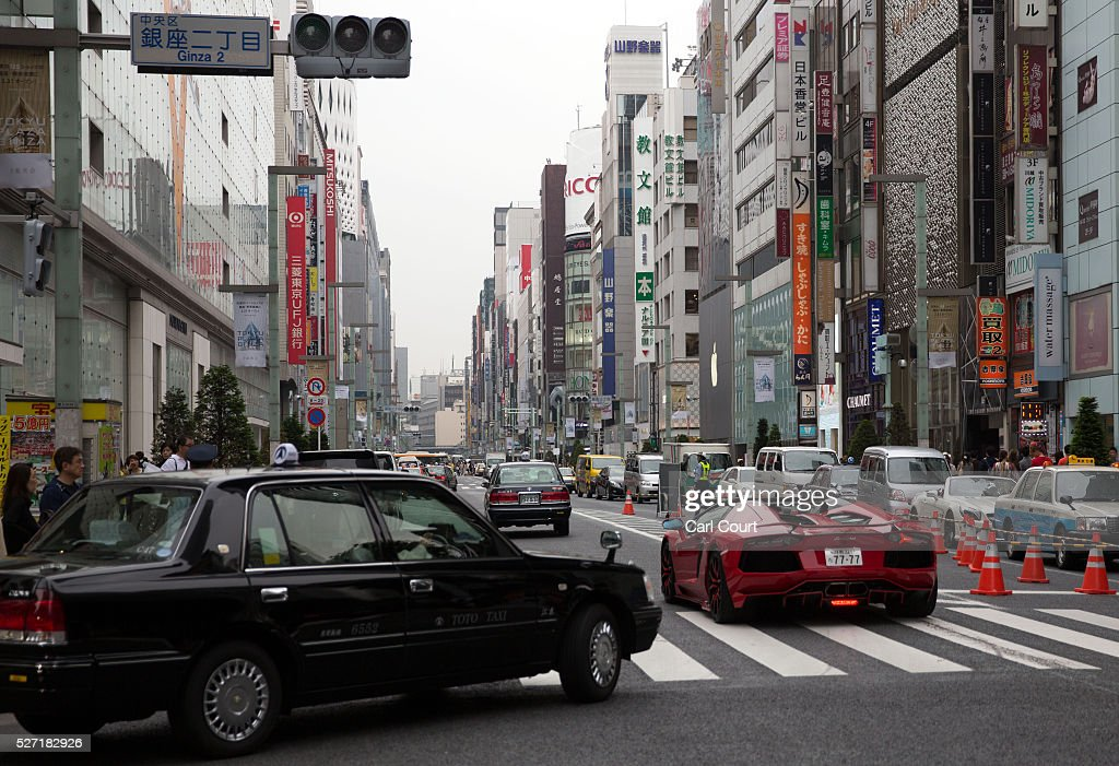 A Lamborghini and taxi are driven on May 02, 2016 in the Ginza area of Tokyo, Japan. The Greater Tokyo Area is the most populous metropolitan area in the world with a population of 13,506,607 and is currently ranked first in the world in the Safe Cities Index.
