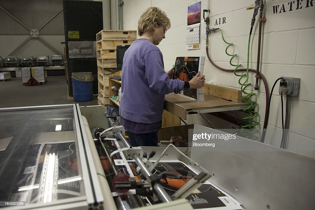 Laminating operator Jeanne Suffrins checks book covers just out of the laminating machine at the Hal Leonard Corp. printing facility in Winona, Minnesota, U.S., on Friday, March 22, 2013. Hal Leonard is the world's largest print music publisher, distributing more than 200,000 titles to over 65 countries. Photographer: Ariana Lindquist/Bloomberg via Getty Images