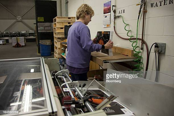 Laminating operator Jeanne Suffrins checks book covers just out of the laminating machine at the Hal Leonard Corp printing facility in Winona...