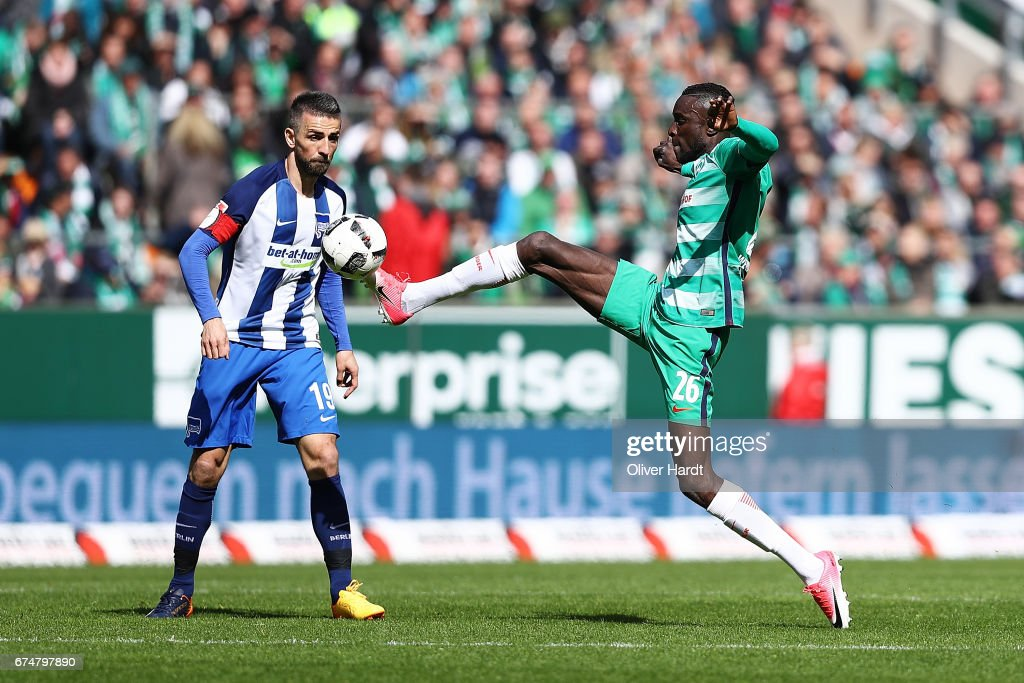 Lamine Sane (R) of Bremen and Vedad Ibisevic (L) of Berlin compete for the ball during the Bundesliga match between Werder Bremen and Hertha BSC at Weserstadion on April 29, 2017 in Bremen, Germany.