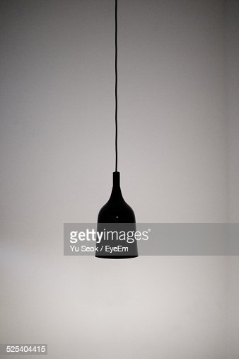 Lamp Hanging From Ceiling Against Wall
