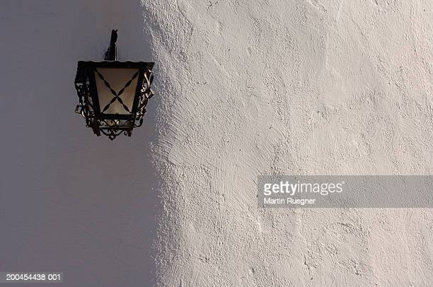 Lamp hanging on white wall