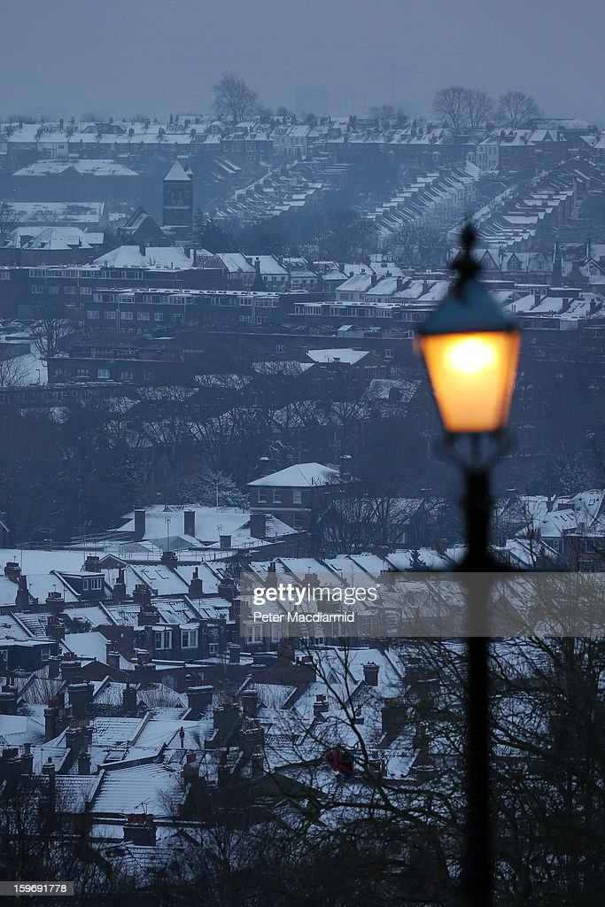 A lamp illuminates the view of snow covered houses near Alexandra Palace on January 18, 2013 in London, England. Severe weather is expected in parts of the United Kingdom today.