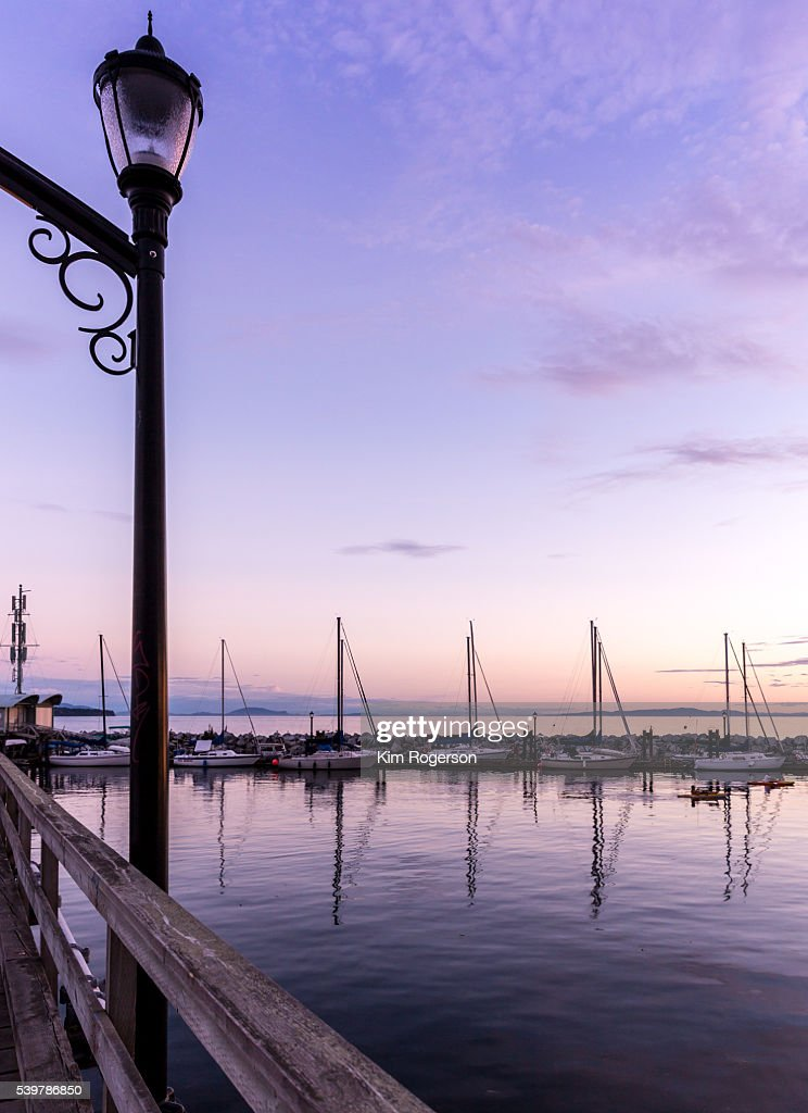 Lamp post of a wooden pier with sailboats in background