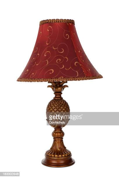 A lamp with a red lampshade on a white background