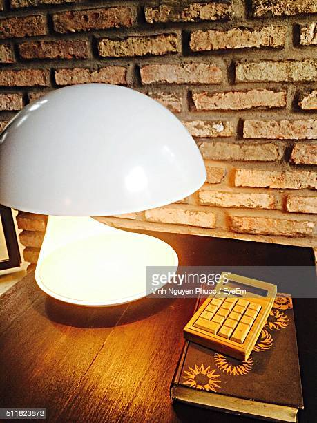 Lamp with calculator and book on table