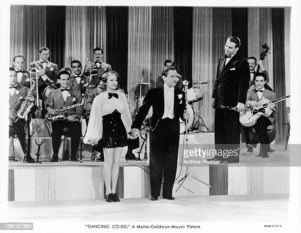 Lana Turner and Roscoe Karns standing before Artie Shaw and his orchestra in a scene from the film 'Dancing Coed' 1939