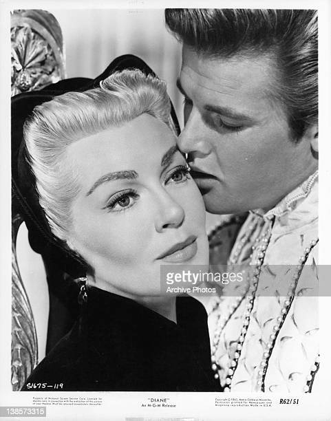 Lana Turner stares forward as Roger Moore seductively kisses her cheek in a scene from the film 'Diane' 1956