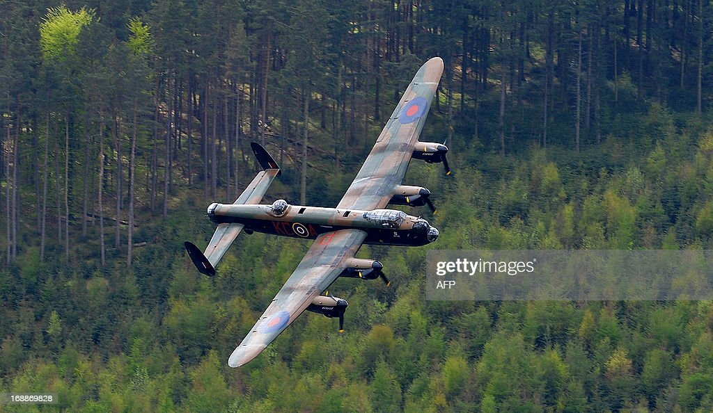 A Lancaster bomber flies over Derwent Reservoir in Derbyshire, England on May 16, 2013, as part of events marking the 70th Anniversary of an air-raid on three dams in Germany's Ruhr Valley by a team of airmen dubbed the 'Dambusters'. A British World War II Lancaster bomber performed a flypast Thursday over a reservoir used for practice runs by the legendary 'Dambusters' airmen to mark 70 years since their daring raid over Nazi Germany's industrial heartland. The four-engined aircraft was joined by two Spitfires and two modern-day Tornado jets as they swept over the Derwent Reservoir in Derbyshire, northern England, where the Royal Air Force trialled the 'bouncing bomb'. AFP PHOTO/ANDREW YATES