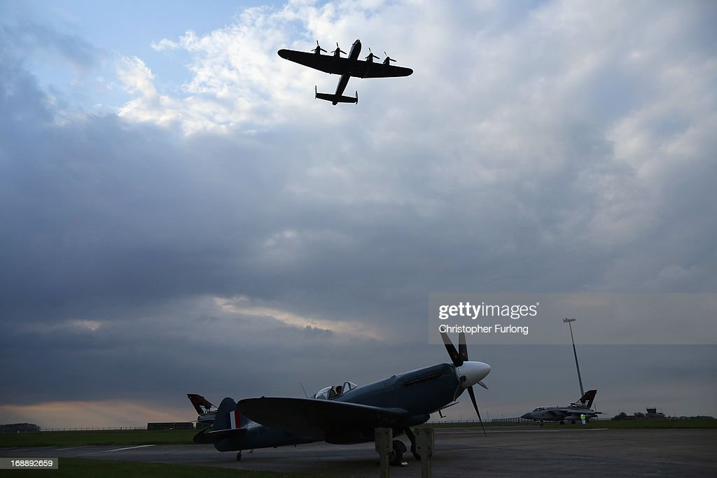 Lancaster Bomber 'The City of Lincoln' flys over a WWII Spitfire as they take part in a Sunset Ceremony to mark the 70th anniversary of the World War II Dambusters mission at RAF Sccampton on May 16, 2013 in Lincoln, England. Ladybower and Derwent reservoirs were used by the RAF's 617 Squadron in 1943 to test Sir Barnes Wallis' bouncing bomb before their mission to destroy dams in Germany's Ruhr Valley. Today marks the 70th anniversary of the famous Dambuster mission and will be watched by veterans from the original campaign.
