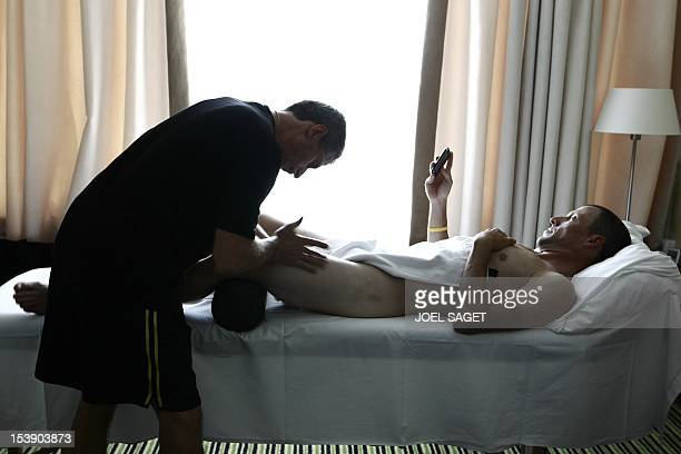 US Lance Armstrong is getting a massage by a physiotherapist as he watches the World Cup 2010 quarterfinal football match Netherlands vs Brazil on...