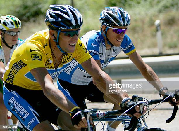 Lance Armstrong of the US and the Discovery Channel team rides in the yellow jersey and talks to teammate Jose Azevedo of Portugal during Stage 18 of...