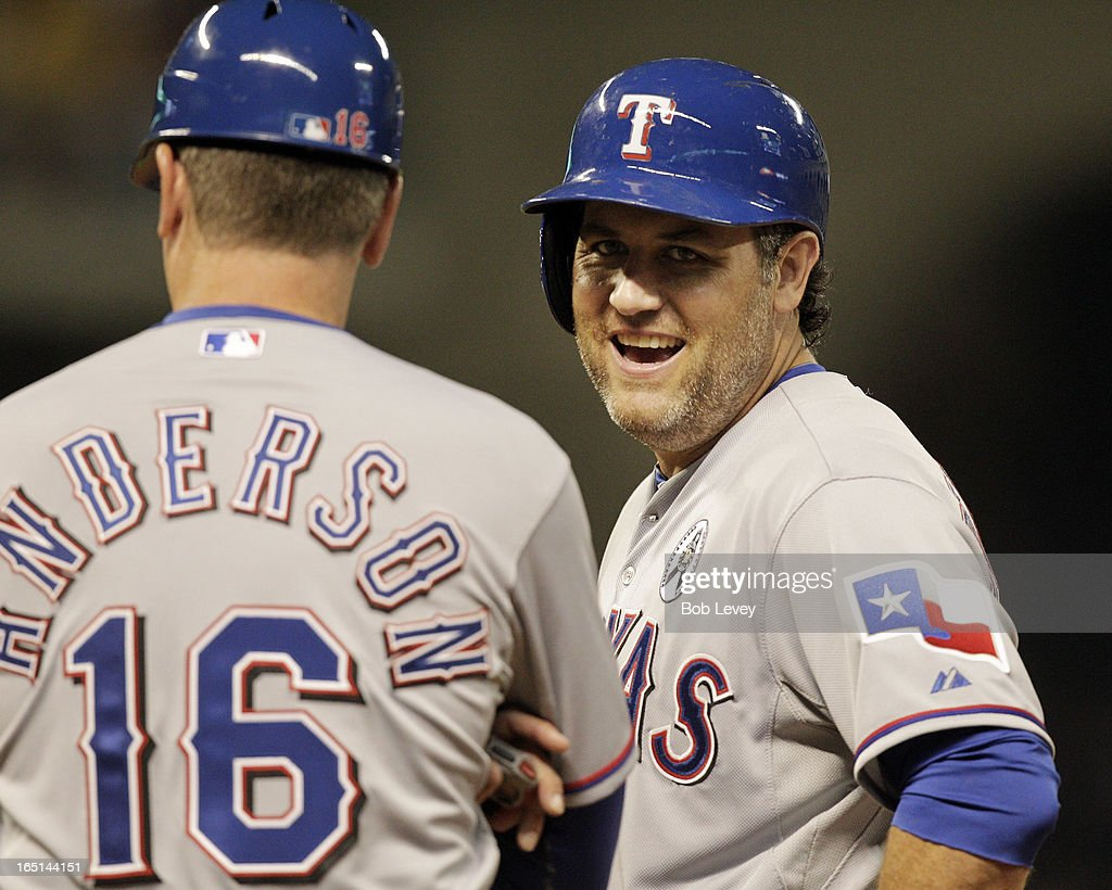 Lance Berkman #27 of the Texas Rangers talks with first base coach Dave Anderson #16 of the Texas Rangers after hitting a single in the sixth inning against the Houston Astros on Opening Day at Minute Maid Park on March 31, 2013 in Houston, Texas.